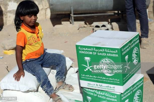 A displaced Yemeni child sits next to boxes of Saudiprovided humanitarian food aid at a camp in Yemen's northeastern province of Marib on January 26...