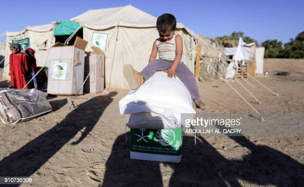 TOPSHOT A displaced Yemeni child sits on boxes and sacks of Saudiprovided humanitarian food aid at a camp in Yemen's northeastern province of Marib...