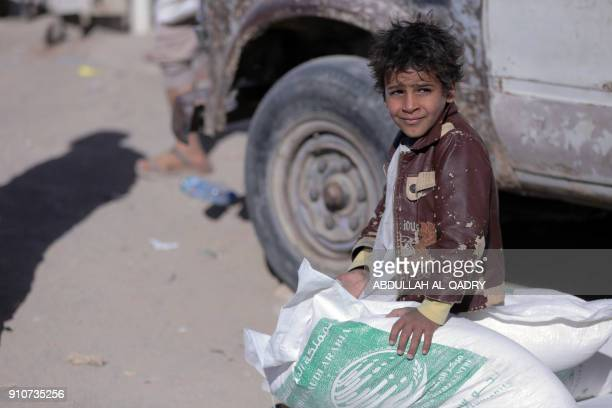 A displaced Yemeni child sits on sacks of Saudiprovided humanitarian food aid at a camp in Yemen's northeastern province of Marib on January 26 2018...