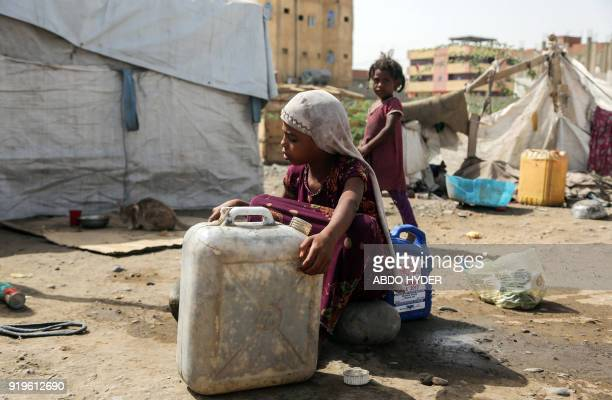 A displaced Yemeni child who fled fighting between the Saudiled coalition and Shiite Huthi rebels tries to carry a container of water at a camp in...