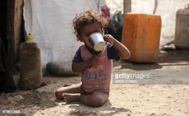 A displaced Yemeni child who fled fighting between the Saudiled coalition and Shiite Huthi rebels drinks from a metal cup while sitting at a camp in...
