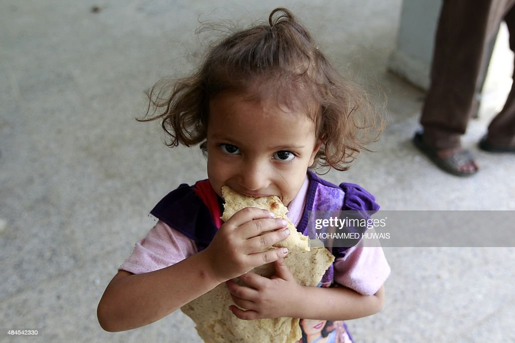 A displaced Yemeni child, who fled Saada province with her family due to fighting between Shiite Huthi rebels and forces loyal to Yemen's exiled President Abedrabbo Mansour Hadi, eats bread at a school turned into a shelter in the capital Sanaa on August 19, 2015. The United Nations warned of a 'developing famine' in Yemen, where more than half a million children are severely malnourished, and pressed for access to its war-torn regions.