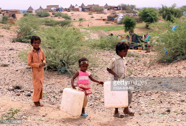 Displaced Yemeni children from Hodeida carry water containers as they walk to a nearby well to fill them at a makeshift camp in a village in the...