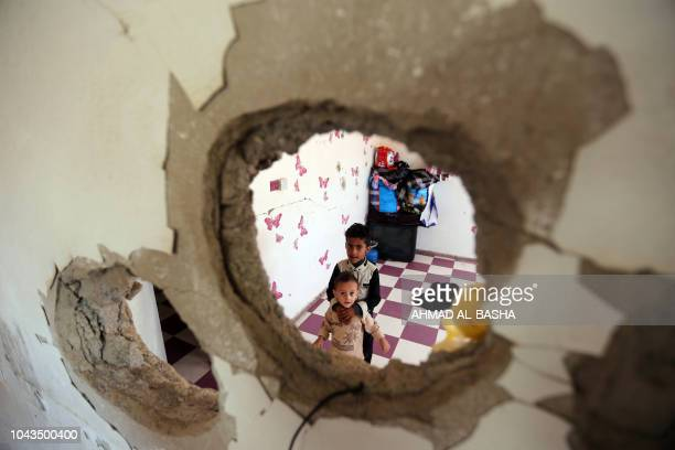 TOPSHOT Displaced Yemeni children from the Hodeidah province are pictured on September 30 2018 through a hole in a damaged house where they have been...