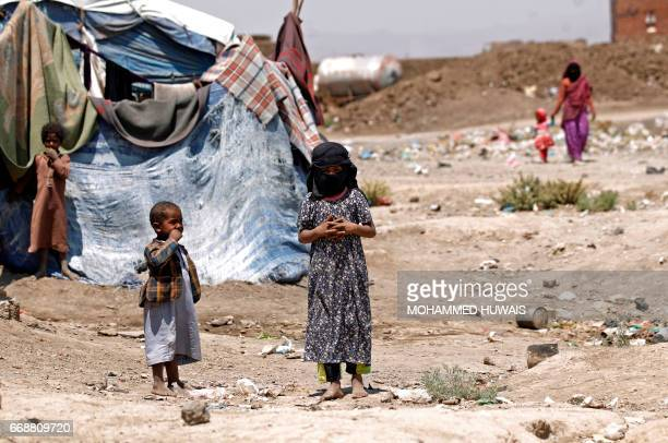 Displaced Yemeni children stand outside a makeshift shelter at a camp for Internally Displaced Persons on the outskirts of Sanaa on April 15 2017 /...