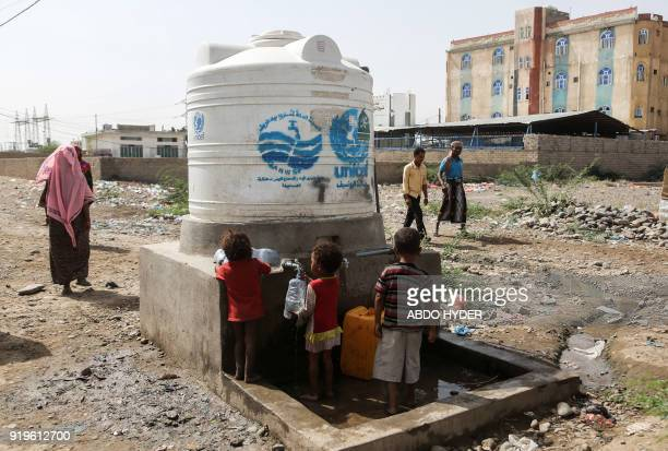 TOPSHOT Displaced Yemeni children who fled fighting between the Saudiled coalition and Shiite Huthi rebels fill up carry containers of water from a...