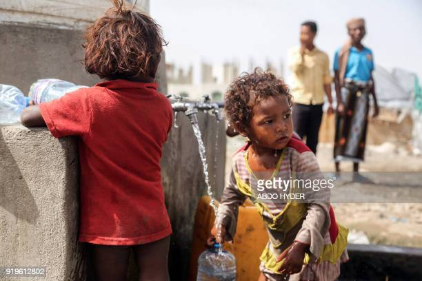 Displaced Yemeni children who fled fighting between the Saudiled coalition and Shiite Huthi rebels fill up carry containers of water from a tap at a...