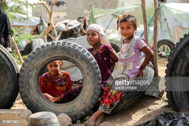 Displaced Yemeni children who fled fighting between the Saudiled coalition and Shiite Huthi rebels sit on tires at a camp in the Yemeni coastal city...
