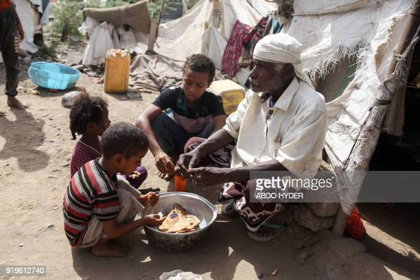 A displaced Yemeni family who fled fighting between the Saudiled coalition and Shiite Huthi rebels gather for a meal as they sit in a camp in the...