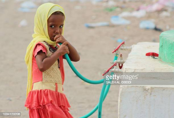 TOPSHOT A displaced Yemeni girl drinks water in a camp set up for people who fled the battle areas east of the port city of Hodeida on September 15...