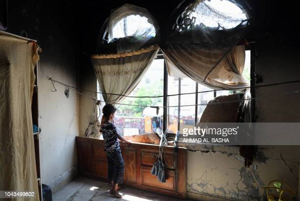 Displaced Yemeni girl looks on September 30, 2018 out of the window of a damaged house where she and her family have been living since they sought...