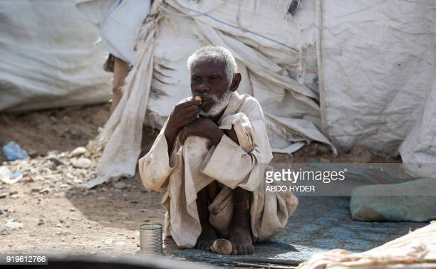 TOPSHOT A displaced Yemeni man who fled fighting between the Saudiled coalition and Shiite Huthi rebels eats while sitting outside a tent at a camp...