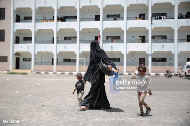 A displaced Yemeni woman and two children who fled their homes in the wartorn port city of Al Hudaydah arrive in Sanaa as clashes intensify in...
