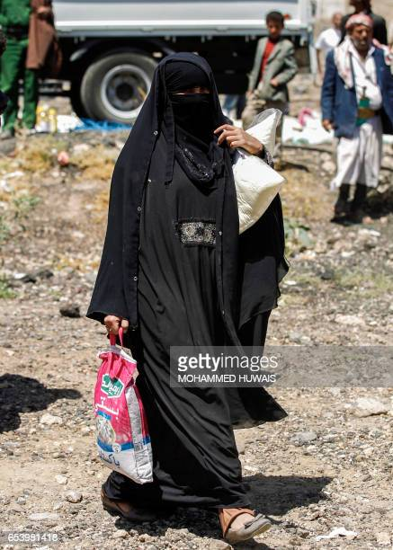 A displaced Yemeni woman carries food aid supplies distributed by the Russian humanitarian relief mission at a camp on the outskirts of the capital...