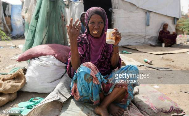A displaced Yemeni woman who fled fighting between the Saudiled coalition and Shiite Huthi rebels eats while sitting outside a tent at a camp in the...