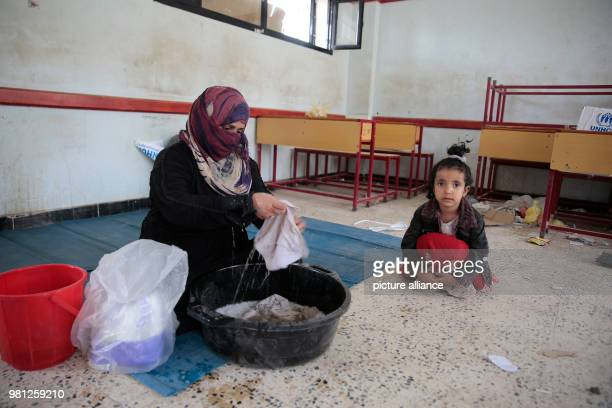 A displaced Yemeni woman who fled her home in the wartorn port city of Al Hudaydah washes clothes at a school as clashes intensify in western coast...