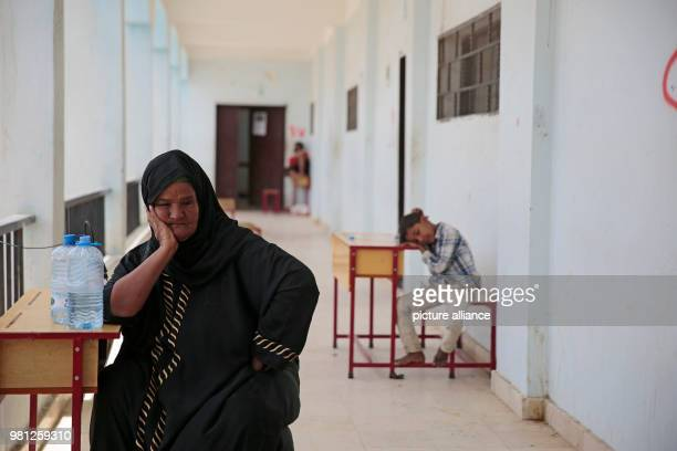 A displaced Yemeni woman who fled her home in the wartorn port city of Al Hudaydah rests after arriving at a school as clashes intensify in western...