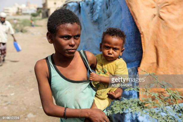 A displaced Yemeni youth who fled fighting between the Saudiled coalition and Shiite Huthi rebels carries a child while walking at a camp in the...