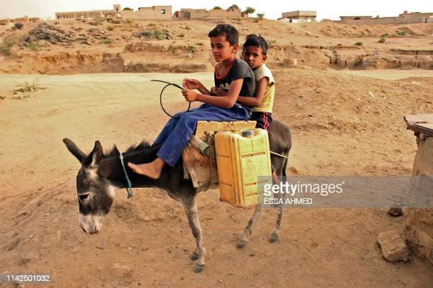 Displaced Yemenis from Hodeida fill water containers at a makeshift camp in a village in the northern district of Abs in the country's Hajjah...