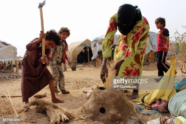 Displaced Yemenis who fled the fighting between the Saudiled coalition and Shiite Huthi rebels in the area of Harad make a fire at a camp for...