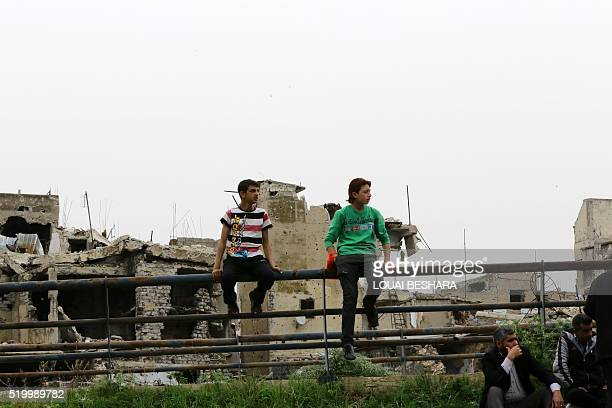 Displaced young Syrians sit on a railing in front of heavily damaged buildings on April 9 2016 in the central Syrian city of Homs as they wait to...