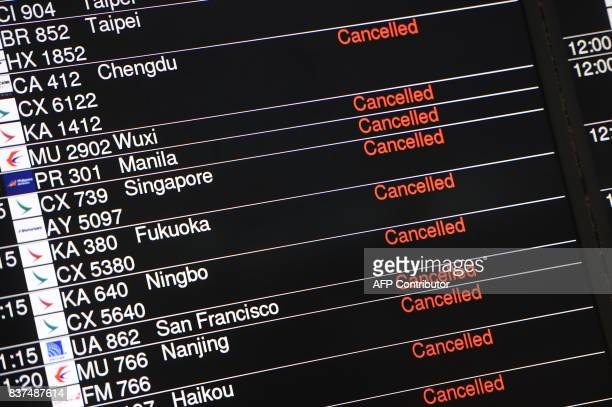 A display board showing flights cancelled due to Typhoon Hato is pictured at the downtown airport checkin station in Hong Kong's Central district on...