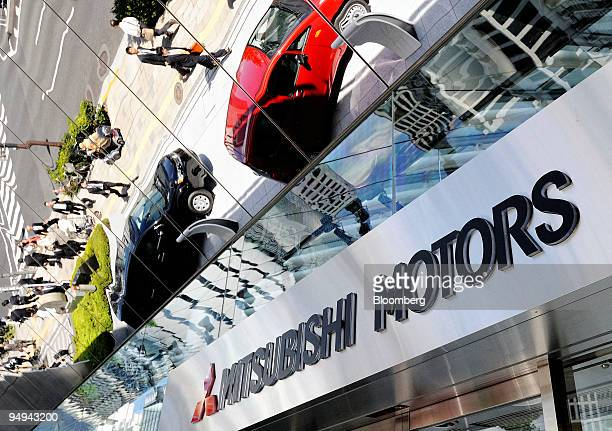 Display cars are reflected in the mirrored entrance to the Mitsubishi Motors Corp head office showroom in Tokyo Japan on Monday April 27 2009...