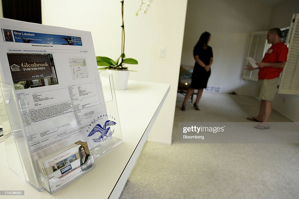 A display for Gina Labellarti, a realtor with Coldwell Banker Dynasty TC, left, is displayed as she speaks with a potential homebuyer during an open house in Arcadia, California, U.S., on Sunday, July 21, 2013. Sales of previously owned houses unexpectedly dropped in June, hurt by a lack of supply and rising mortgage rates that may slow the rebound in the U.S. real-estate market. Photographer: Jonathan Alcorn/Bloomberg via Getty Images