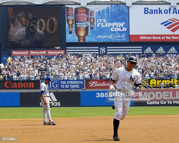 A display in the background at Yankee Stadium shows the achievement of New York Yankees' Alex Rodriguez as he rounds the bases after hitting his...