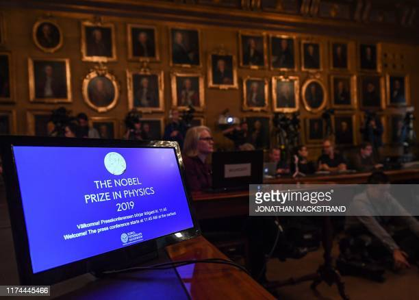 A display is seen as journalists await the announcement of the winners of the 2019 Nobel Prize in Physics at the Royal Swedish Academy of Sciences on...