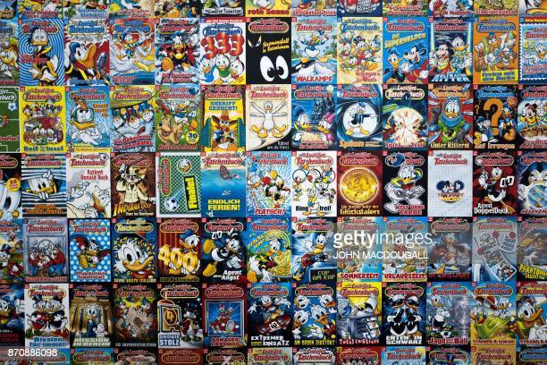 A display made up of hundreds of covers of Donald Duck pocket books called 'Lustiges Taschenbuch' in German and featuring Disney comics is seen on...