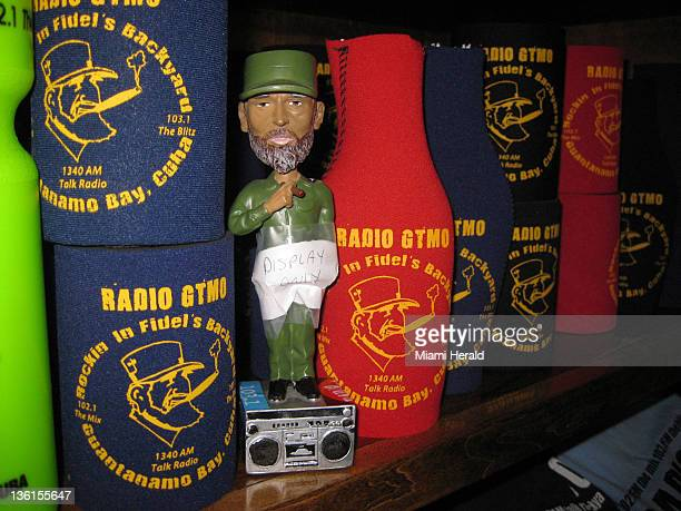 A display model of a $25 Fidel Castro bobblehad doll peeks out from a shelf of drink cozies emblazoned with the Radio GTMO slogan at the US Navy base...