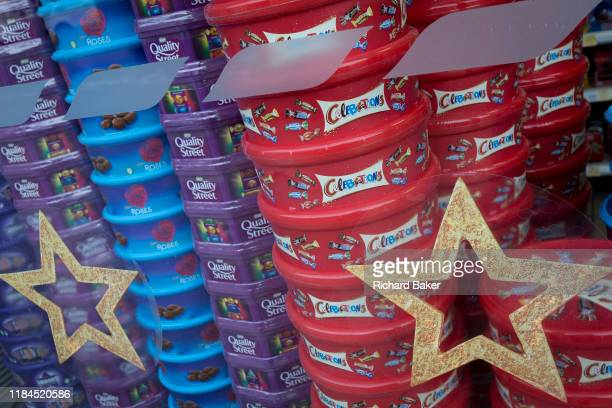 Display of assorted chocolate and sweet boxes of Nestle Quality Street, Cadburys Roses and Heroes plus Mars Celebrations piled up in the Christmas...