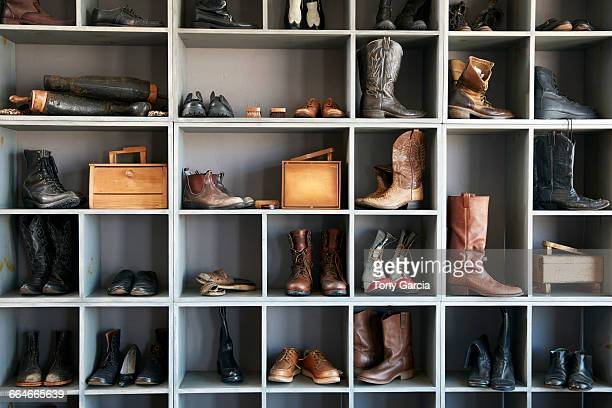 display of boots and shoes on shelves in traditional shoe shop - schuhwerk stock-fotos und bilder