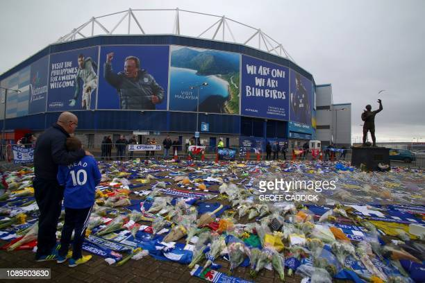 TOPSHOT A display of Cardiff City scarves and jerseys flowers messages and other tributes to the football club's new signing Emiliano Sala whose...