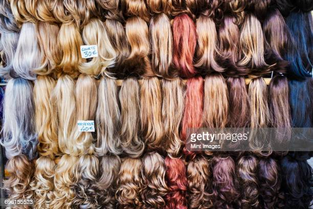 a display of hair extensions and hair pieces of different colours. - wig stock pictures, royalty-free photos & images