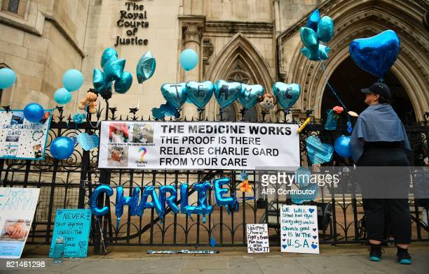 A display of messages posters and balloons set up by supporters of the family of British baby Charlie Gard are seen outside the Royal Courts of...