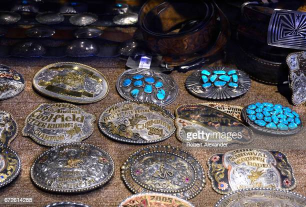 A display of rodeo trophy belt buckles and silver Native American buckles set with turquoise for sale in a western wear consignment shop in Santa Fe...