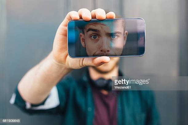 display of smartphone showing young man pulling funny face - horizontal stock-fotos und bilder