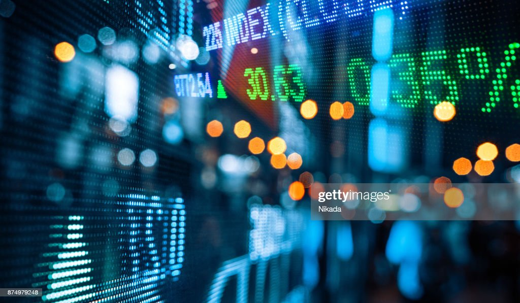 Display of Stock market quotes with city scene reflect on glass : Stock Photo