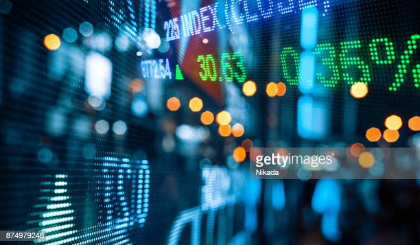 display of stock market quotes with city scene reflect on glass - finanza foto e immagini stock
