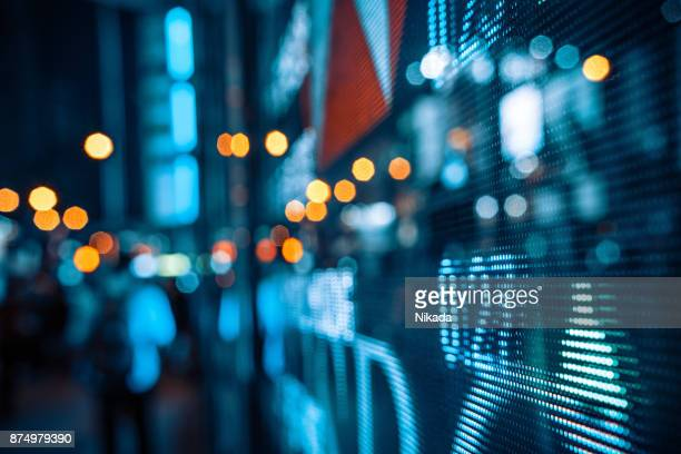display of stock market quotes with city scene reflect on glass - interest rate stock pictures, royalty-free photos & images