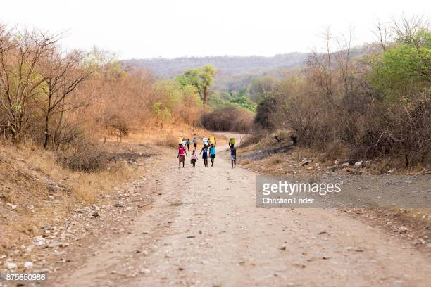Displaying four teenager and a small girl with a dog, carrying plastic buckets filled with water on their head, walking towards the camera on a sand...