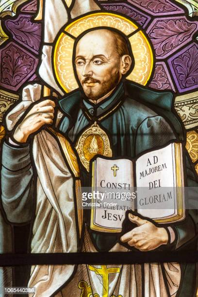 Displaying the mosaic window with Ignatius of Loyola holding the constitutionbook from the the society of Jesus On the odd page is written Ad majorem...