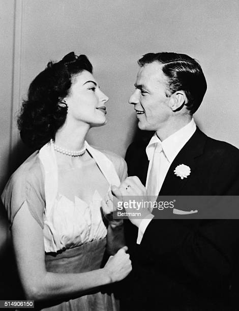 Displaying their wedding bands film actress Ava Gardner and crooner Frank Sinatra gaze at each other following their wedding at the home of a friend...