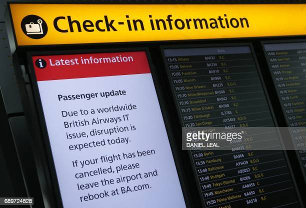 A displays warning passengers to 'Expect Disruption' to British Airways flights is pictured inside Terminal 5 of London's Heathrow Airport on May 29...