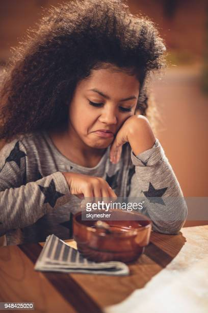 displeased african american girl doesn't want to eat her breakfast. - complaining stock photos and pictures