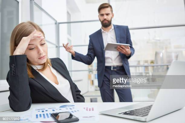 Displeased boss berating indifferent employee