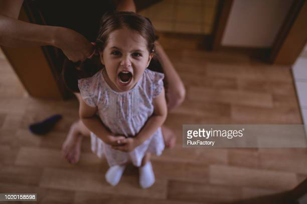 unzufrieden kind und ihre mutter machen frisuren - reizen stock-fotos und bilder