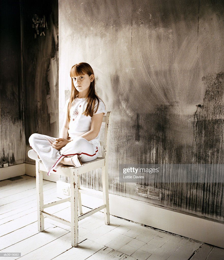 Displeased Looking Girl Sitting Cross Legged on a Wooden Chair in a Room With The Walls Painted in Black : Stock Photo